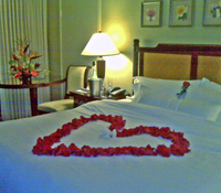 Maui Honeymoon Special showing heart of petals on the bed and floral tropical arrangement.