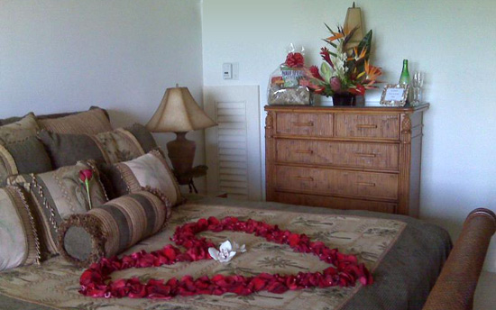 Maui Honeymoon Special. Rose petal heart on bed, tropical arrangment and munchies gift basket